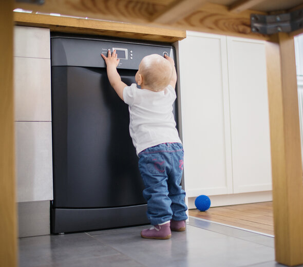 A one year old child is standing in the kitchen with dishwasher and is pressing buttons on the control panel of the dishwasher. He is wearing blue trousers and a bright shirt. A navy ball lies on the floor.