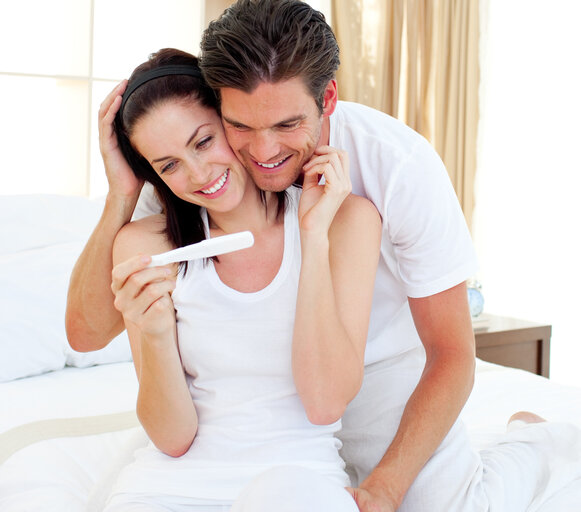 The man is hugging from behind a woman who is holding a pregnancy test in her hand. They are smiling. The couple looks happy that their family will grow.