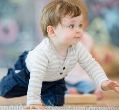 A few-month-old baby is wearing navy blue pants and a striped long-sleeved body. The baby taking his first steps on all fours. Baby began his crawling adventure.