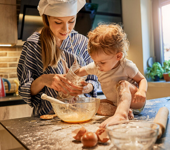A young mother spends time with her several-month-old baby in the kitchen. A woman is making cookies with the baby. The infant is sitting on the counter alone and is helping mom in cooking.