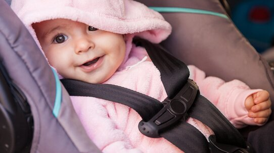 A recently born baby with a wide smile ia sitting calmly in a baby car seat. Baby is wearing in a pink sweatshirt with tiny ears sewn on the hood.