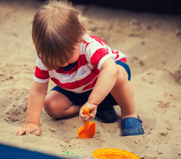A dozen months old baby is outside, in the open air. The infant is playing in the sand by gouging in it with a blue spatula. The child is sitting alone on sand in the sandbox.