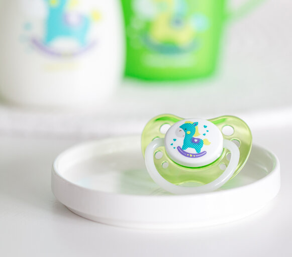 On a white, small plate on the dresser lying a green soother with a rocking horse motif. The selection of a suitable teat is very important for the development of the speech apparatus.