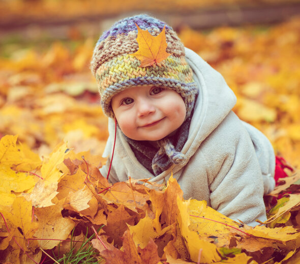A smiling infant sits on the ground in a park amongst a pile of yellowed leaves. The little one has a colorful wool cap on his head, on which lies an orange leaf.